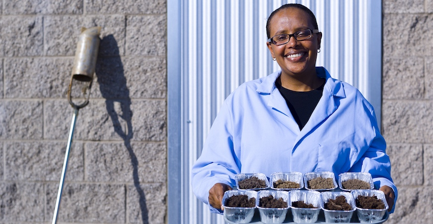 Professor Asmeret Asefaw Berhe stands in front of a wall wearing a light blue lab coat and holding a tray of cake tins filled with soil samples.