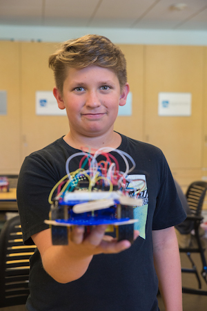 A middle school student looks into the camera. His hand holds a small robotic device. He holds this robotic device in front of him, arm outstretched toward the camera.