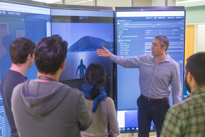 A man points to a three large monitors while four students face him and listen to his explanation.