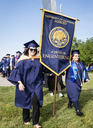 Bethany Trinidade ('09) and Heather Hopkins ('09) return to UC Merced as flag bearers at the spring 2019 commencement for the schools of Natural Sciences and Engineering.