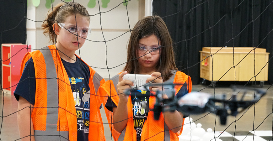 Two kids flying a drone at the Mobile Maker Space at the Merced County Fair.