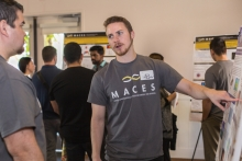 A student discusses his research poster during the MACES event.