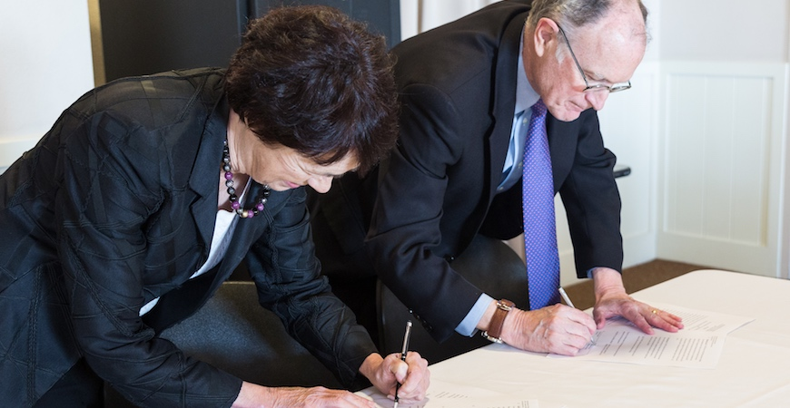 Chancellor Dorothy Leland and Berkeley Lab Director Michael Witherell sign MOU agreement on a white table.
