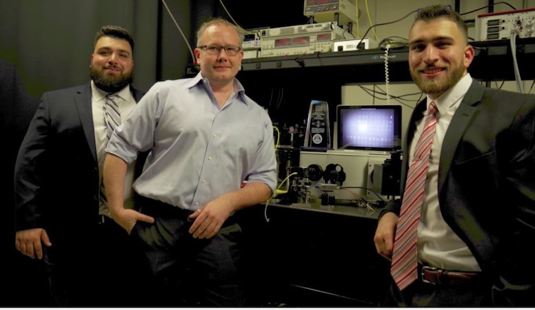 Three men pose in front of scientific equipment.