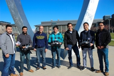 UC Merced's NASA Swarmathon team poses in front of campus's Beginnings sculpture.